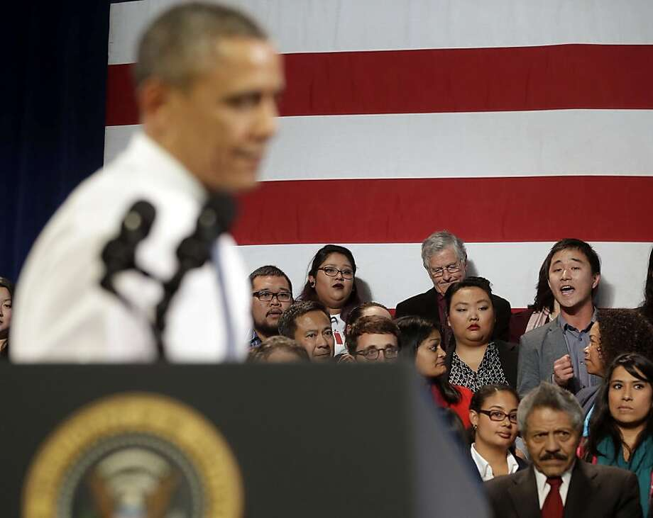 Immigrant Ju Hong (right) interrupts a speech about immigration policy by President Obama in Chinatown. Photo: Pablo Martinez Monsivais, Associated Press