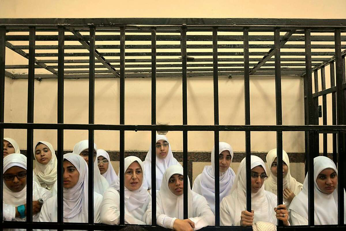 Harsh justice: Supporters of ousted President Mohammed Morsi stand inside the defendants' cage in a courtroom in Alexandria, Egypt. The court sentenced 21 female Morsi supporters, some of them teenagers, to 11-year prison terms for holding a protest.