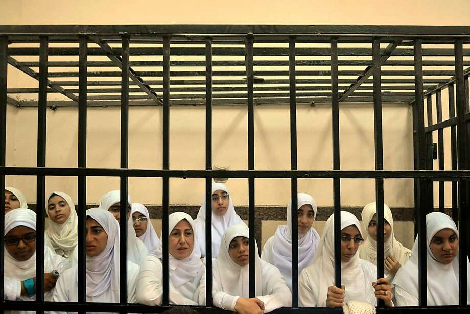 Harsh justice: Supporters of ousted President Mohammed Morsi stand inside the defendants' cage in a courtroom 
