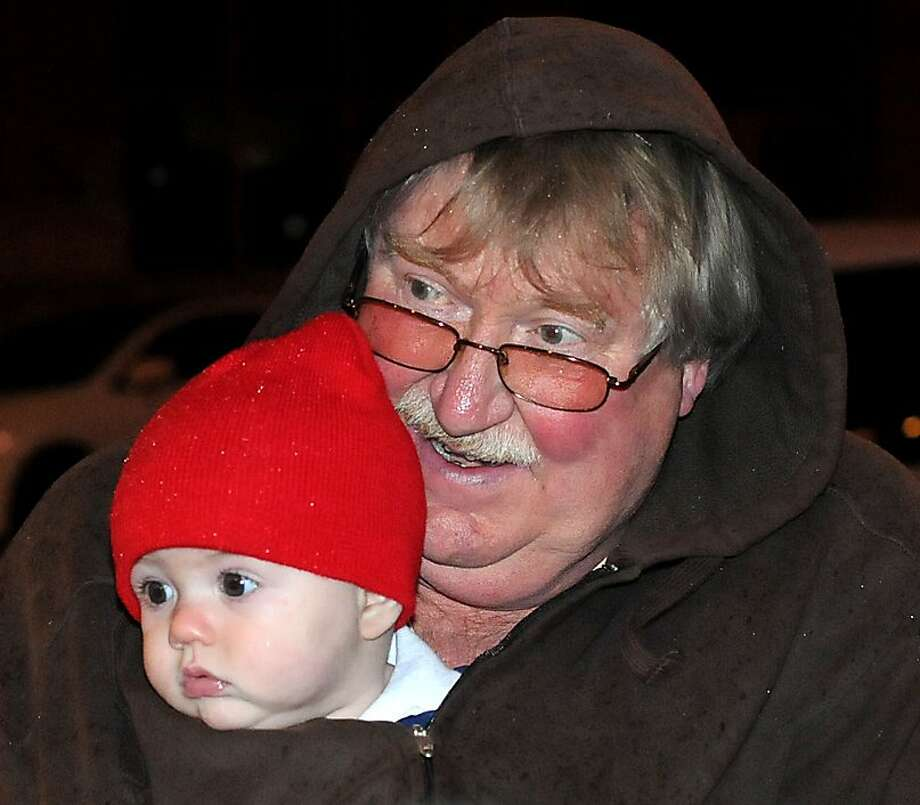 When holidays collide: Frank Morrison holds his 5-month-old grandson, Kayden Bowling, inside his coat while 