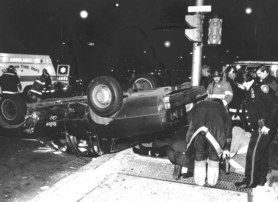 Emergency workers help a cab driver who was injured in an accident at Washington Boulevard and Main Street on Dec. 1, 1988. Photo: File Photo, Advocate / Advocate