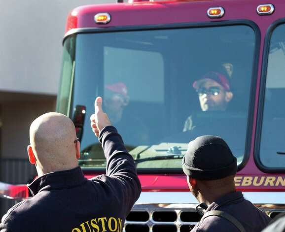 Houston Fire Department Capt. Todd Kahney gives a thumbs up to Capt. Bill Dowling as he is released from the hospital Wednesday, Nov. 27, 2013, in Houston. Dowling has been hospitalized since the deadly motel fire on May 31. Dowling rode home in HFD Engine 68. Photo: Brett Coomer, Houston Chronicle / © 2013 Houston Chronicle
