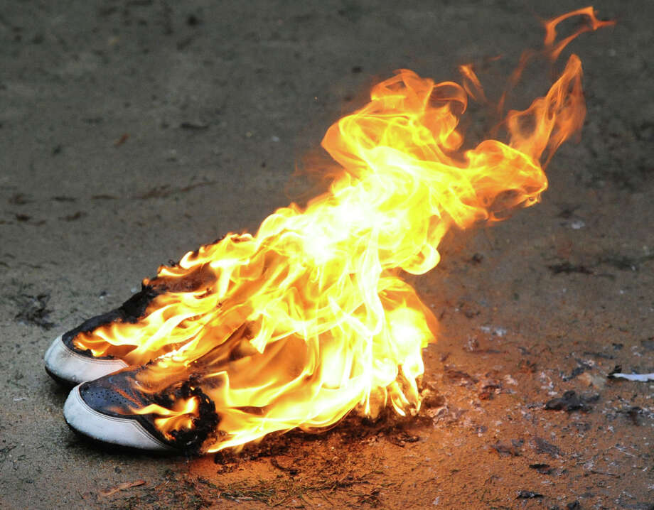 A pair of football shoes are burned during the annual Greenwich High School Football team's burning of the shoes ceremony at Cardinal Stadium, Greenwich, Wednesday afternoon, Nov. 27, 2013. The ceremony symbolizes the transition of seniors out of the football program, burning their shoes demonstrates that they can never be filled again. Photo: Bob Luckey / Greenwich Time