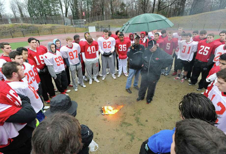 Greenwich High School Football Coach, Rich Albonizio, at center, speaks with his team during the annual Greenwich High School Football team's burning of the shoes ceremony at Cardinal Stadium, Greenwich, Wednesday afternoon, Nov. 27, 2013. The ceremony symbolizes the transition of seniors out of the football program, burning their shoes demonstrates that they can never be filled again. Photo: Bob Luckey / Greenwich Time