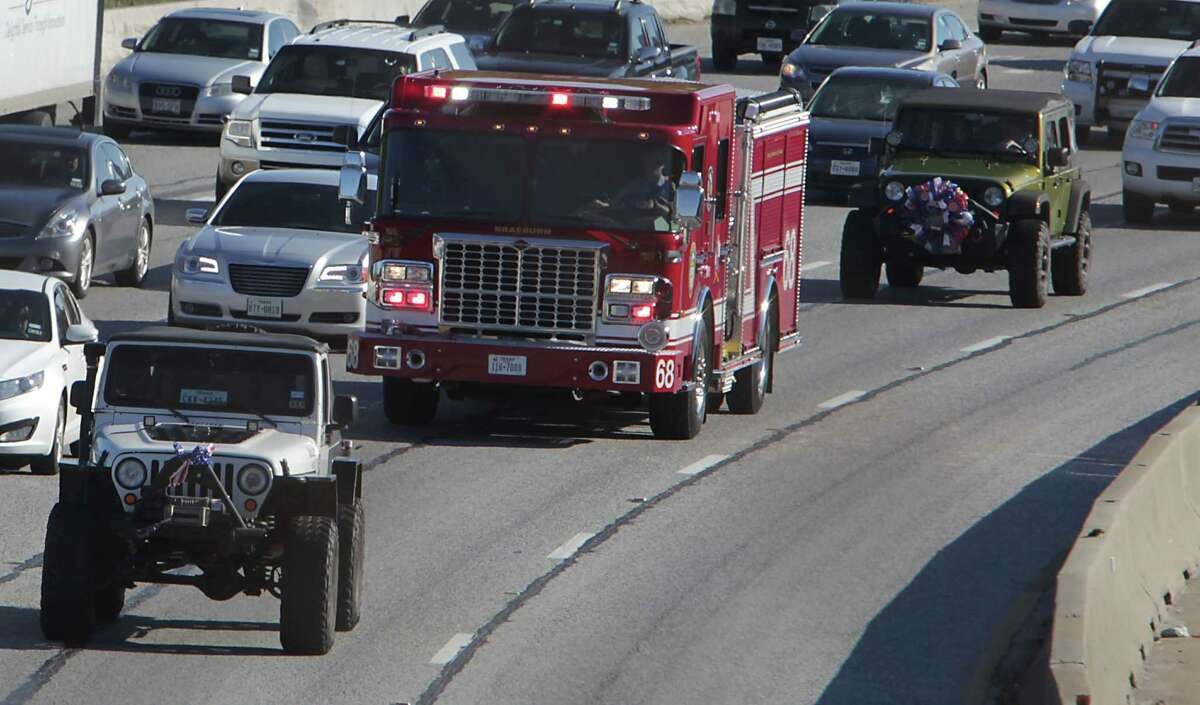 Houston Arson Investigators salute as a procession with HFD Captain Bill Dowling drives along the North Freeway, after Dowling was released from the hospital due to injuries in the massive Southwest Freeway hotel fire in May, Wednesday, Nov. 27, 2013, in Houston.