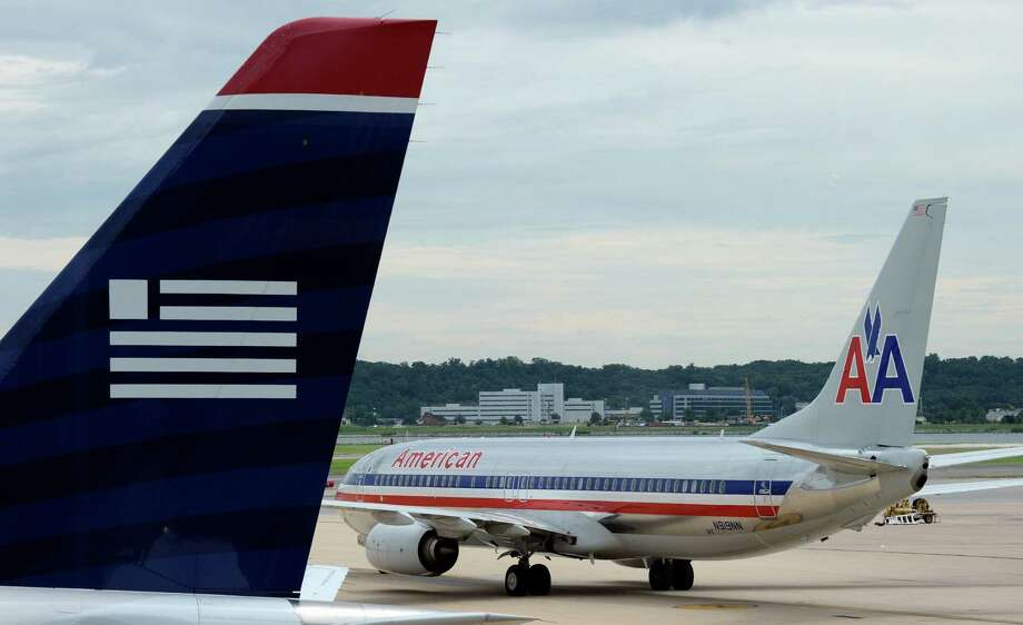 FILE - In this  Tuesday, Aug. 13, 2013, file photo, an American Airlines plane and a US Airways plane are parked at Ronald Reagan National Airport in Washington. A Federal bankruptcy judge is approving the settlement in the U.S. government's antitrust lawsuit against American Airlines and US Airways, clearing the airlines to complete their merger early December 2013. (AP Photo/Susan Walsh, File) ORG XMIT: NYBZ135 Photo: Susan Walsh / AP