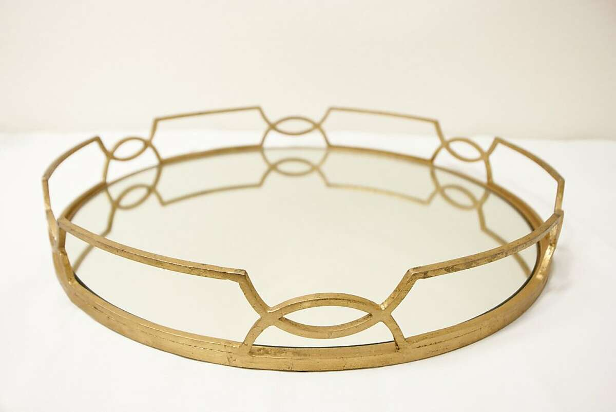 ENTERTAINING: A swank, swanky, swankiest round mirrored tray that helps a harried host with a raised rail of graphic interlocking curves to corral those craft cocktails, caviar canapes or cardamom holiday cookies, $540, http://mytallulah.com. Shown with a gold leaf finish, it's available in silver leaf as well.