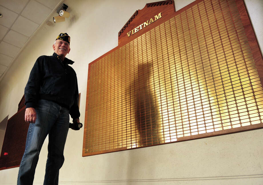 Army veteran Eric Muth poses next the Vietnam memorial that hangs inside the lobby of the Parsons Government Center Auditorium in Milford, Conn. on Wednesday November 27, 2013. Muth is on a mission to get the names of all the veterans to be listed near the various war monuments located on the Milford Green instead of the auditorium where access is limited. Photo: Christian Abraham / Connecticut Post