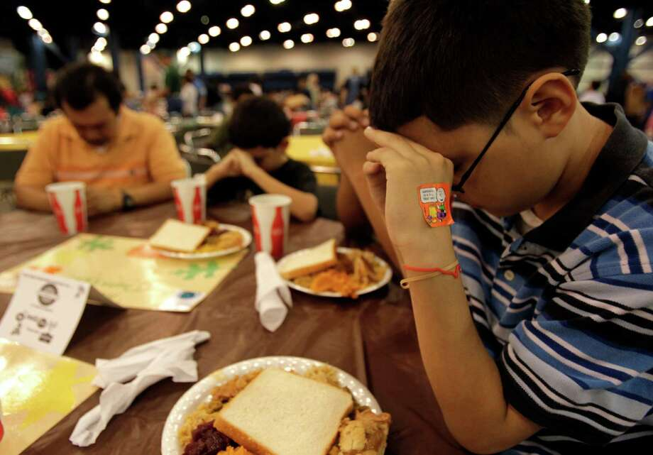 Eric Lopez, 10, prays with his family of six before eating a Thanksgiving lunch during The City Wide Club of Clubs 26th Feast of Big Sharing Feast at the George R. Brown Convention Center in 2010. Photo: Johnny Hanson, Staff / Houston Chronicle