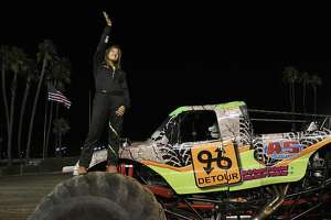 Rosalee Ramer, 16, waves to a cheering crowd after getting introduced by the announcer as she stands on her truck, Detour, before her evening performance Sept. 27, 2013, at the LA County Fairgrounds in Pomona, Calif. Rosalee started driving monster trucks at age 14, becoming the youngest female monster truck driver in the world, a title she still holds today at age 16. Ramer has grown up around the sport and around cars in general. Her father, Kelvin Ramer, owns a tow-truck business in Watsonville and has been driving his own monster truck for most of Rosalee's life.