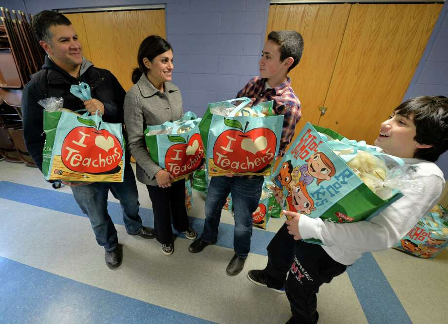 T. J. Tracy, 13 is surrounded by family which includes his father Chris Ermides, left mom Beverly, second from left and his little brother Josh, 11 as brought their food donation to the Franklin Community Center Monday afternoon Nov 25, 2013, in Saratoga Springs, N.Y.        (Skip Dickstein/Times Union) Photo: SKIP DICKSTEIN / 00024777A