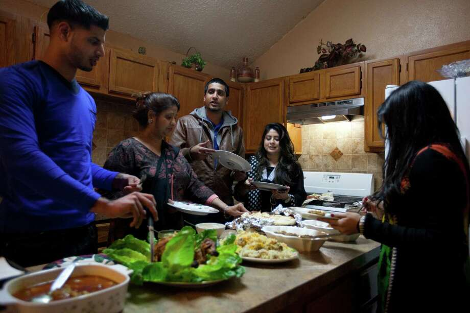 Fareed Mian, 22, left, takes a helping of home-cooked dinner with his fiancee Yousra Yasin, far right, and his mother, Khalida Mian. His brother Mueed, 23, center, and his fiancee Anh Azam join a hybrid Pakistani-American tradition. Photo: Marie D. De Jeséºs, Staff / © 2013 Houston Chronicle