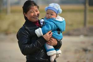 A grandmother carries her grandson in the village of Gangzhong in China's eastern Zhejiang province on November 19, 2013.  Days after the conclusion of a key internal gathering known as the Third Plenum, China's ruling party leadership unveiled a list of sweeping changes to economic and social policy. They included reforms to the country's land ownership system, loosening controls over state-owned enterprises, relaxing the controversial one-child policy and eventually shuttering forced labour camps.      AFP PHOTO / Peter PARKSPETER PARKS/AFP/Getty Images