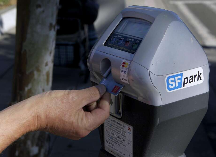A commuter uses a debit card to pay for a parking meter on The Embarcadero in San Francisco on Friday, June 28, 2013. Photo: Paul Chinn, The Chronicle
