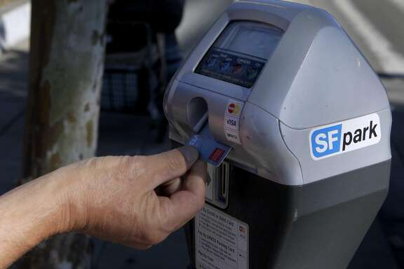 A commuter uses a debit card to pay for a parking meter on The Embarcadero in San Francisco, Calif. on Friday, June 28, 2013. The violation for parking at expired meters jumps to $74 on July 1, making it the most expensive fine in the country.
