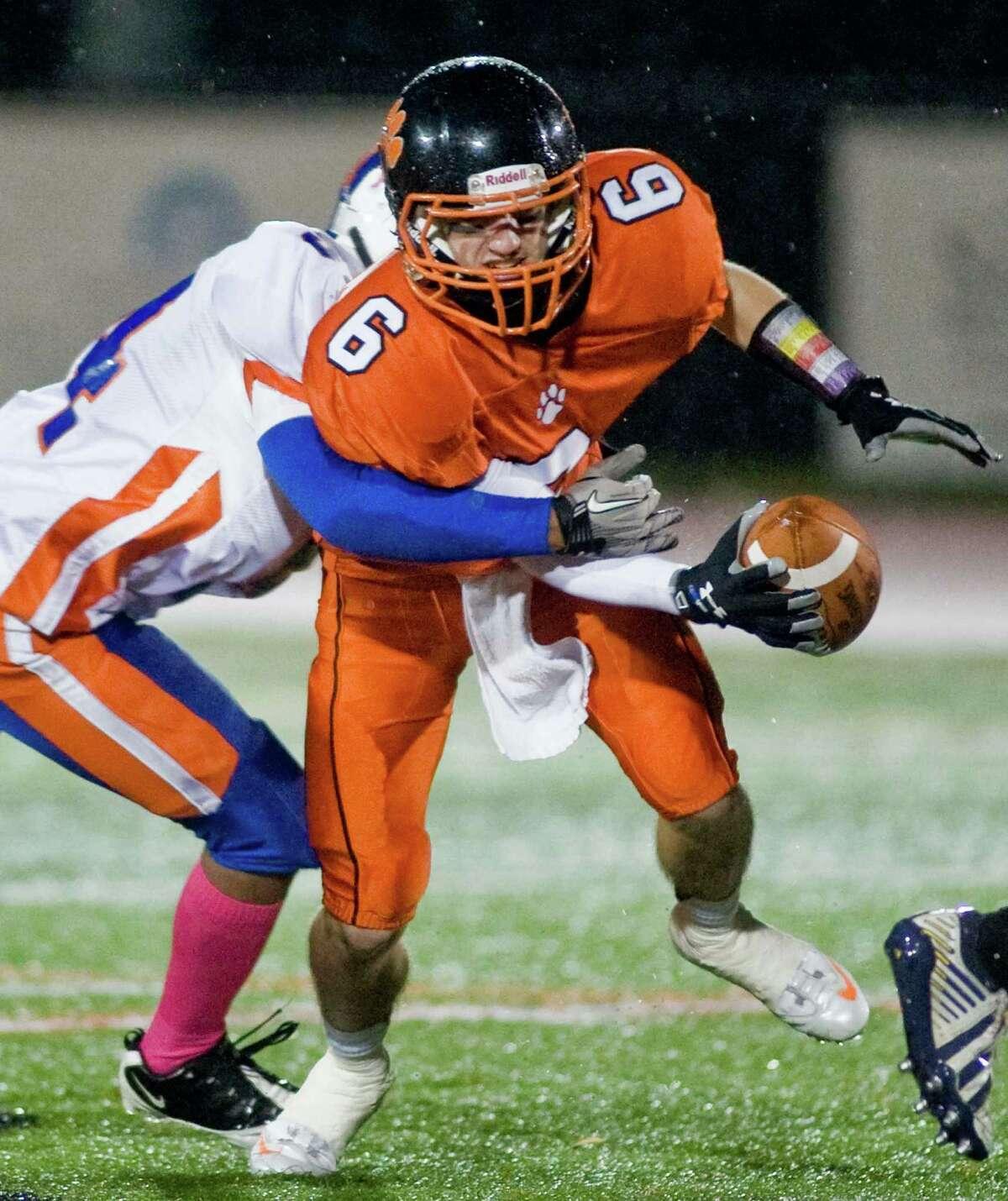 Ridgefield High School quarterback Ryan Dunn tries to break a tackle in a game against Danbury High School, played at Ridgefield. Wednesday, Nov. 27, 2013