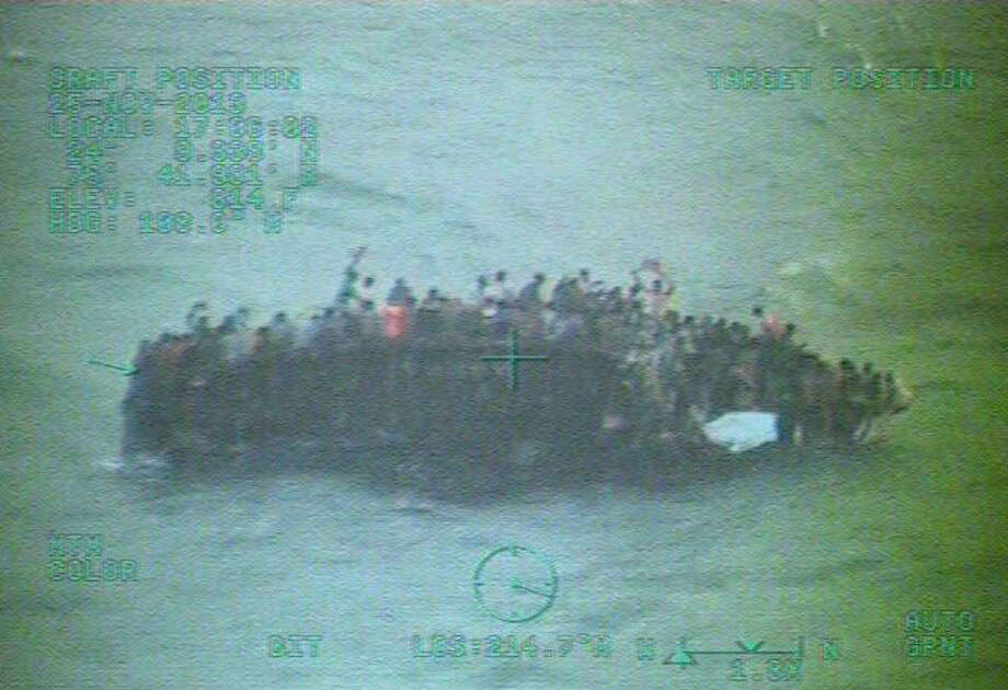 An image from video provided by the U.S. Coast Guard shows Haitian immigrants on the hull of their capsized sailboat in the Bahamas. Officials believe 30 of the immigrants have died. Photo: Associated Press