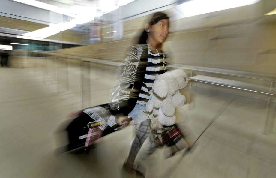 Arianna Meredon, 9, of Albuquerque, N.M., makes her way through Dallas' Love Field airport, in town to watch the Cowboys and visit an aunt who is a cheerleader for the team. Photo: LM Otero / Associated Press