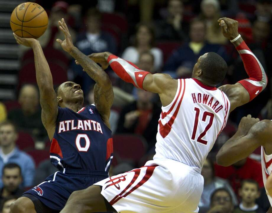 Rockets power forward Dwight Howard (12) defends a shot by Hawks point guard Jeff Teague (0) Photo: Brett Coomer, Houston Chronicle
