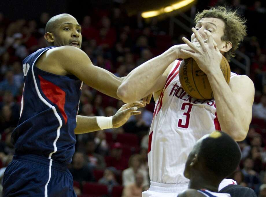 Rockets center Omer Asik (3) pulls a rebound away from Hawks center Al Horford (15). Photo: Brett Coomer, Houston Chronicle