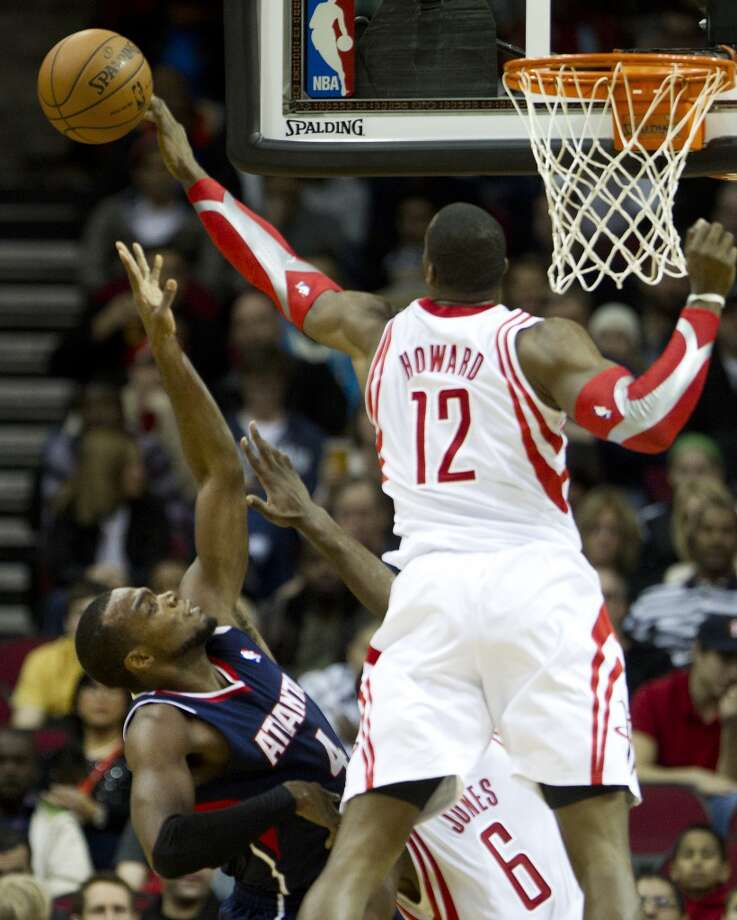 Rockets power forward Dwight Howard (12) blocks a shot by Hawks power forward Paul Millsap (4). Photo: Brett Coomer, Houston Chronicle