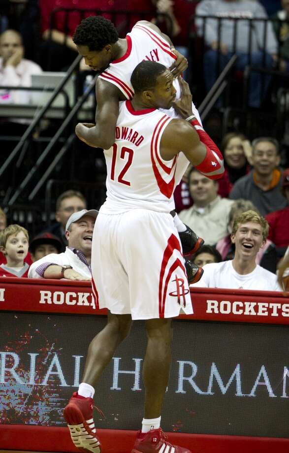 Rockets power forward Dwight Howard (12) helps guard Patrick Beverley (2) down from an advertising board. Photo: Brett Coomer, Houston Chronicle