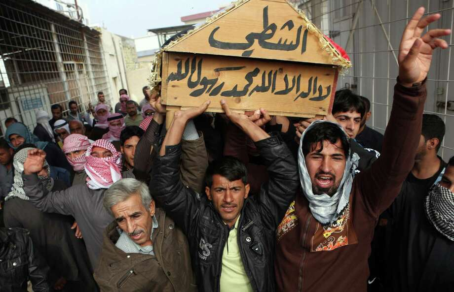 Mourners chant slogans against sectarianism while carrying the coffin of a Sunni tribal sheik at his funeral in Basra, Iraq. The sheik had been kidnapped. Photo: Nabil Al-Jurani / Associated Press