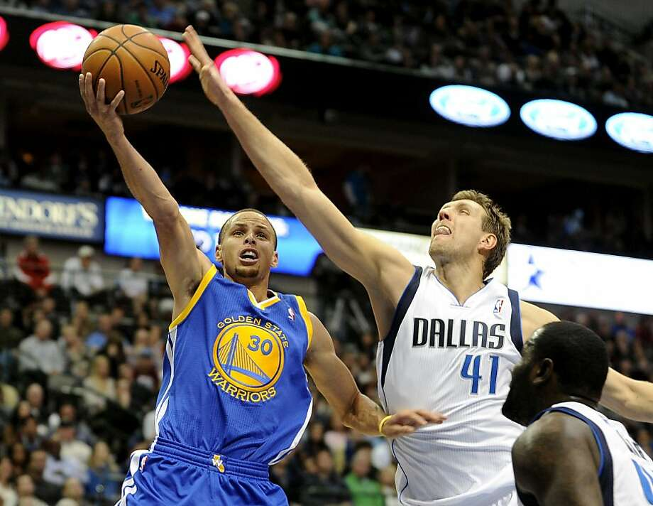 Dirk Nowitzki (41) tries to put the kibosh on a Stephen Curry drive in the second half. Curry scored 13 in the fourth quarter. Photo: Matt Strasen, Associated Press