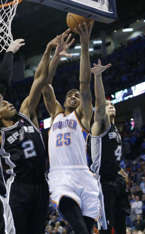 Oklahoma City Thunder guard Thabo Sefolosha (25) shoots between San Antonio Spurs forward Kawhi Leonard (2) and guard Danny Green (4) in the first quarter of an NBA basketball game in Oklahoma City, Wednesday, Nov. 27, 2013. (AP Photo/Sue Ogrocki) Photo: Associated Press