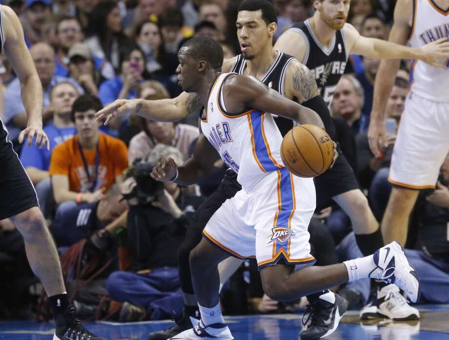 Oklahoma City Thunder guard Reggie Jackson (15) drives around San Antonio Spurs guard Danny Green (4) in the fourth quarter of an NBA basketball game in Oklahoma City, Wednesday, Nov. 27, 2013. Oklahoma City won 94-88. (AP Photo/Sue Ogrocki) Photo: Associated Press