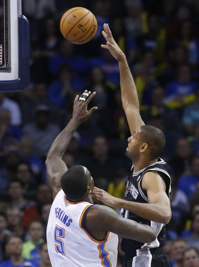 San Antonio Spurs forward Tim Duncan (21) shoots over Oklahoma City Thunder center Kendrick Perkins (5) in the first quarter of an NBA basketball game in Oklahoma City, Wednesday, Nov. 27, 2013. (AP Photo/Sue Ogrocki) Photo: Associated Press