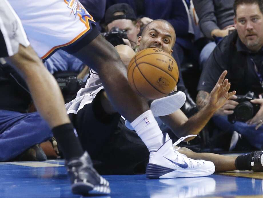 San Antonio Spurs guard Tony Parker (9) passes off after falling down in the second quarter of an NBA basketball game against the Oklahoma City Thunder in Oklahoma City, Wednesday, Nov. 27, 2013. (AP Photo/Sue Ogrocki) Photo: Associated Press