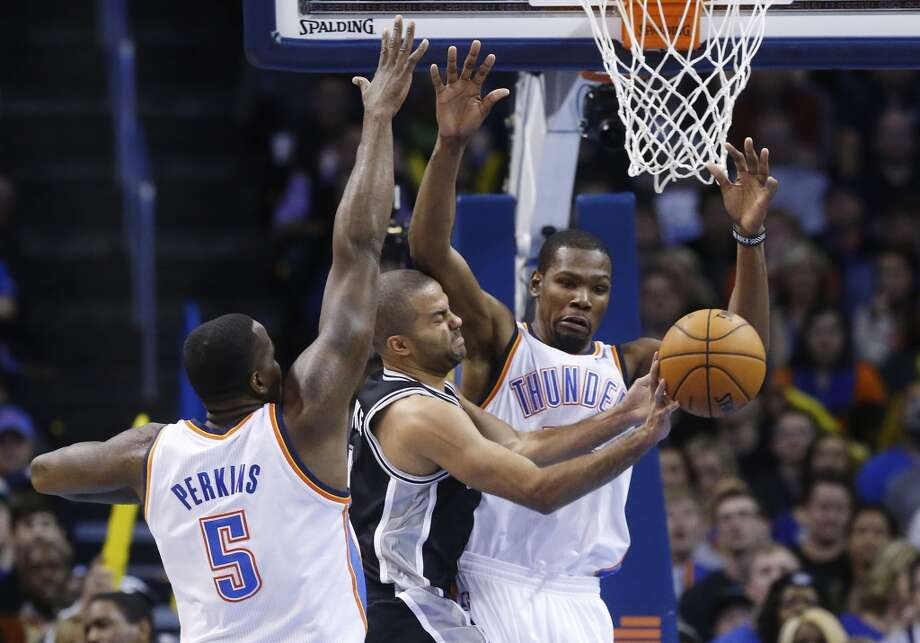 San Antonio Spurs guard Tony Parker (9) passes off between Oklahoma City Thunder center Kendrick Perkins (5) and forward Kevin Durant (35) in the second quarter of an NBA basketball game in Oklahoma City, Wednesday, Nov. 27, 2013. (AP Photo/Sue Ogrocki) Photo: Associated Press