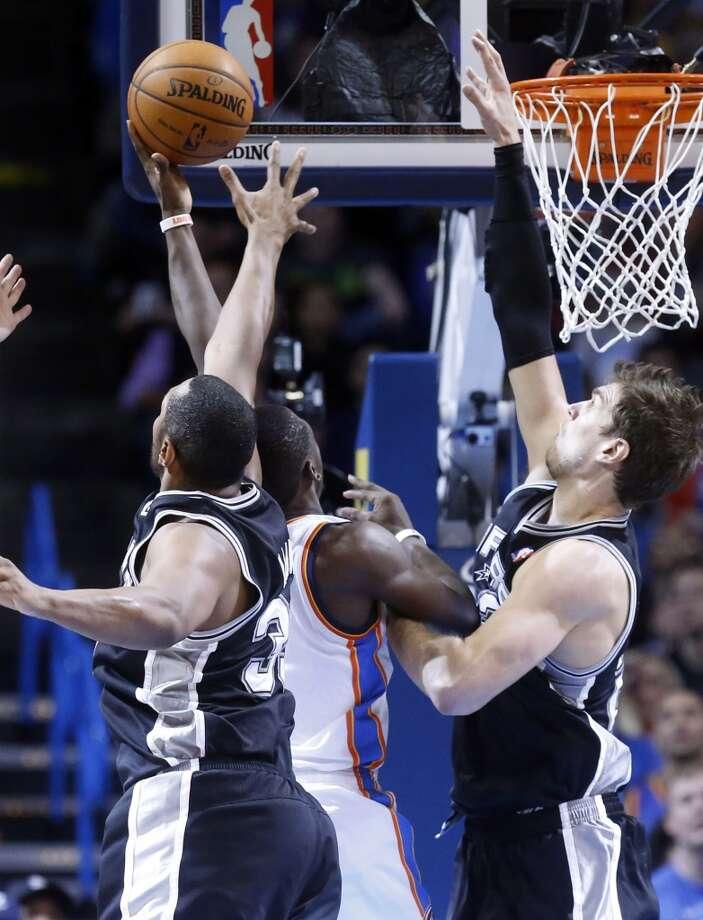 Oklahoma City Thunder guard Reggie Jackson (15) shoots between San Antonio Spurs forward Boris Diaw (33) and center Tiago Splitter (22) in the third quarter of an NBA basketball game in Oklahoma City, Wednesday, Nov. 27, 2013. Oklahoma City won 94-88. (AP Photo/Sue Ogrocki) Photo: Associated Press