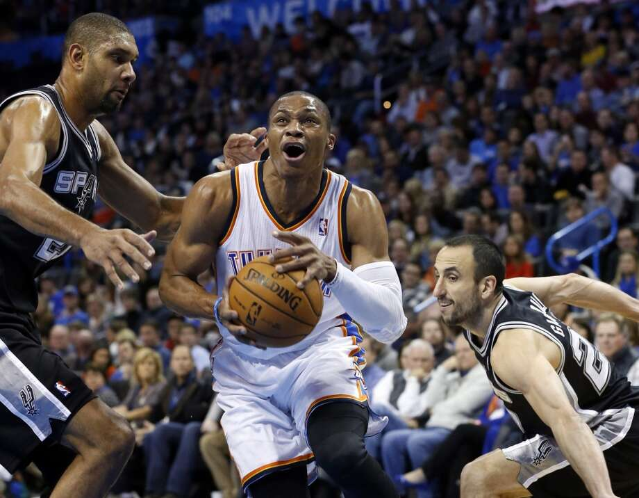 Oklahoma City Thunder guard Russell Westbrook (0) drives between San Antonio Spurs forward Tim Duncan (21) and guard Manu Ginobili (20) in the first quarter of an NBA basketball game in Oklahoma City, Wednesday, Nov. 27, 2013. (AP Photo/Sue Ogrocki) Photo: Associated Press