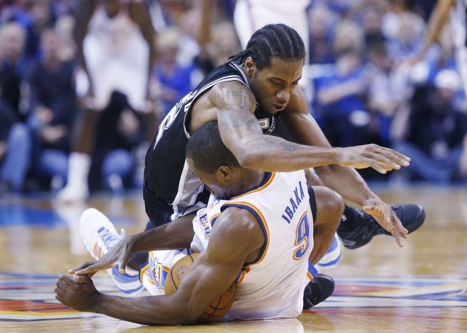 San Antonio Spurs forward Kawhi Leonard (2) lands on Oklahoma City Thunder forward Serge Ibaka (9) after the two chases a loose ball in the third quarter of an NBA basketball game in Oklahoma City, Wednesday, Nov. 27, 2013. Oklahoma City won 94-88. (AP Photo/Sue Ogrocki) Photo: Associated Press
