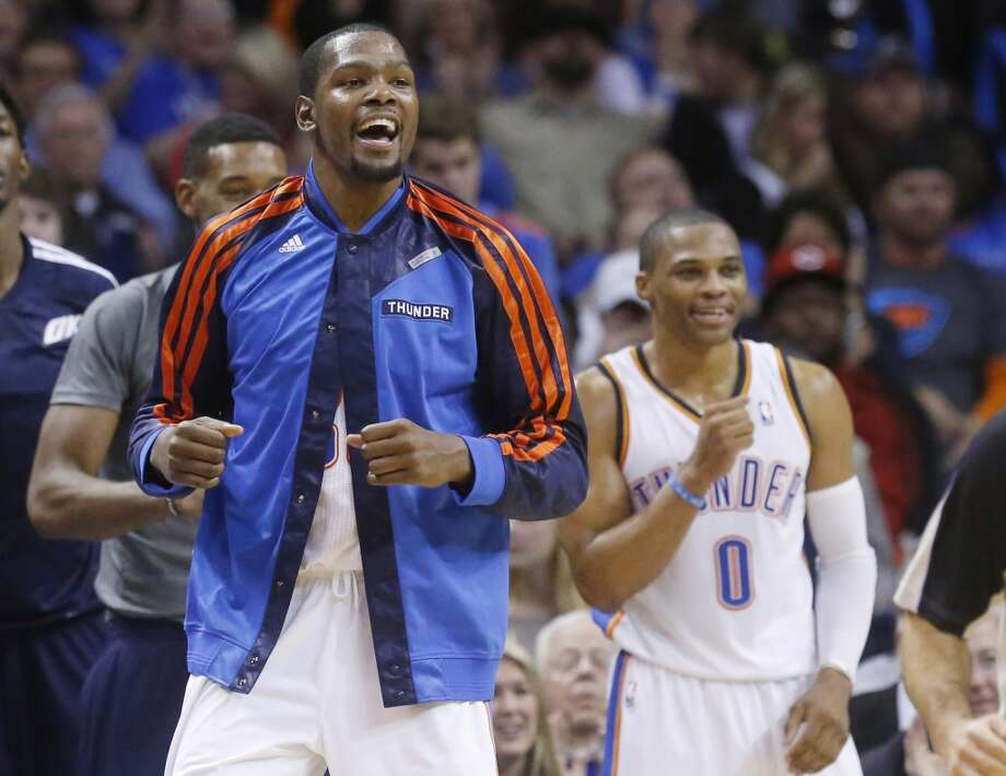 Oklahoma City Thunder forward Kevin Durant, left, and guard Russell Westbrook (0) cheer from the bench in the third quarter of an NBA basketball game against the San Antonio Spurs in Oklahoma City, Wednesday, Nov. 27, 2013. Oklahoma City won 94-88. (AP Photo/Sue Ogrocki) Photo: Associated Press
