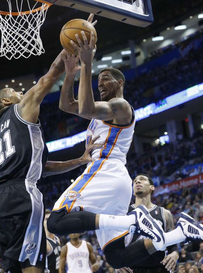 Oklahoma City Thunder guard Thabo Sefolosha (25) passes in front of San Antonio Spurs forward Tim Duncan (21) in the first quarter of an NBA basketball game in Oklahoma City, Wednesday, Nov. 27, 2013. (AP Photo/Sue Ogrocki) Photo: Associated Press