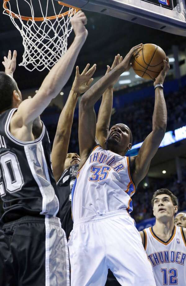 Oklahoma City Thunder forward Kevin Durant (35) shoots in front of San Antonio Spurs guard Manu Ginobili (20) and forward Boris Diaw (33) in the first quarter of an NBA basketball game in Oklahoma City, Wednesday, Nov. 27, 2013. Thunder center Steven Adams (12) is at right. (AP Photo/Sue Ogrocki) Photo: Associated Press