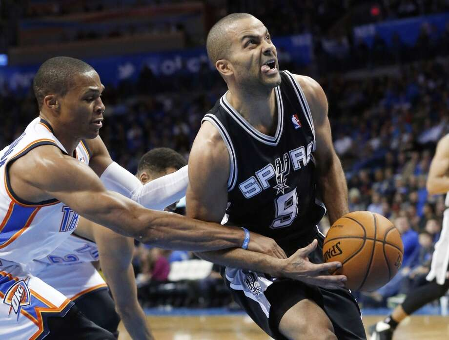 San Antonio Spurs guard Tony Parker (9) is fouled by Oklahoma City Thunder guard Russell Westbrook (0) in the third quarter of an NBA basketball game in Oklahoma City, Wednesday, Nov. 27, 2013. Oklahoma City won 94-88. (AP Photo/Sue Ogrocki) Photo: Associated Press