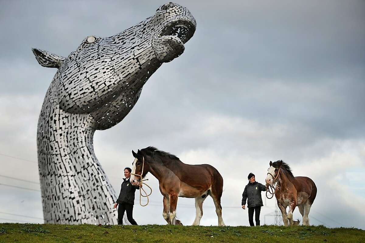 FALKIRK, SCOTLAND - NOVEMBER 27: Donna Auchinvole with Duke and Lorraine Clark with Barron, Clydesdale Horses, attend a topping out ceremony at The Kelpies on November 27, 2013 in Falkirk, Scotland. Construction work has been completed on Andy Scott's Kelpies, the world's largest pair of equine sculptures and one of the UKs tallest pieces of public art. The 30 metre tall Kelpies have cost £5million to complete and play a central role in the £43 million, 350-hectare Helix land transformational project between Falkirk and Grangemouth. (Photo by Jeff J Mitchell/Getty Images) *** BESTPIX ***