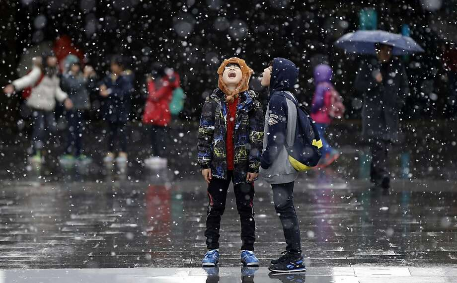 Snack time:Schoolkids try to catch snowflakes on their tongues in Seoul, South Korea. Photo: Lee Jin-man, Associated Press