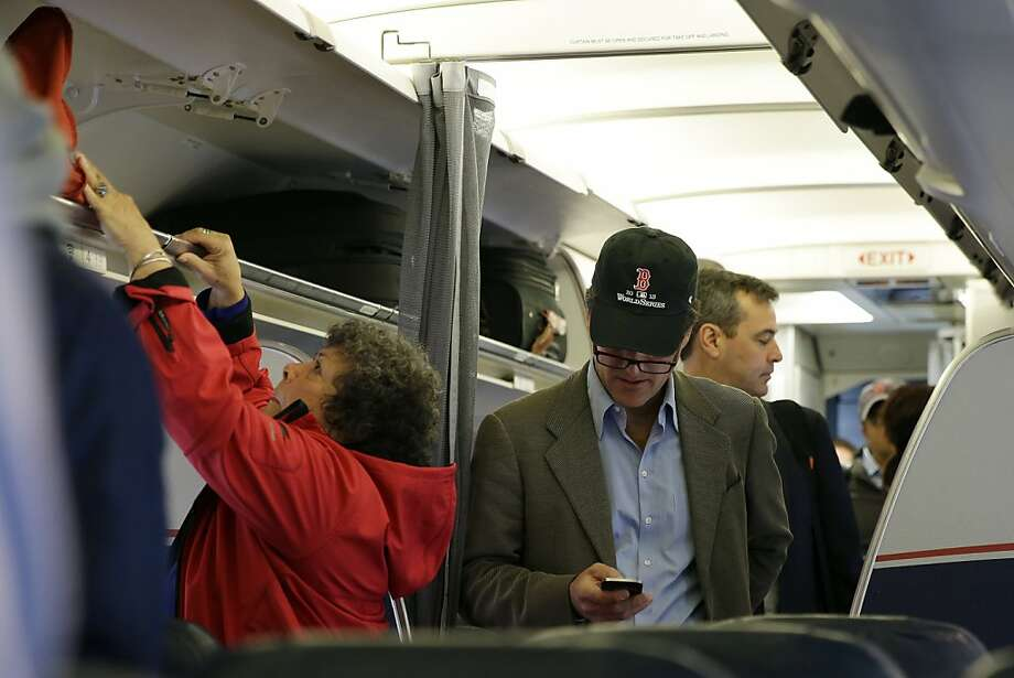A passenger check his cell phone while boarding a flight, Thursday, Oct. 31, 2013, in Boston. The Federal Aviation Administration issued new guidelines Thursday, under which passengers will be able to use devices to read, work, play games, watch movies and listen to music, from the time they board to the time they leave the plane. (AP Photo/Matt Slocum) Photo: Matt Slocum, Associated Press