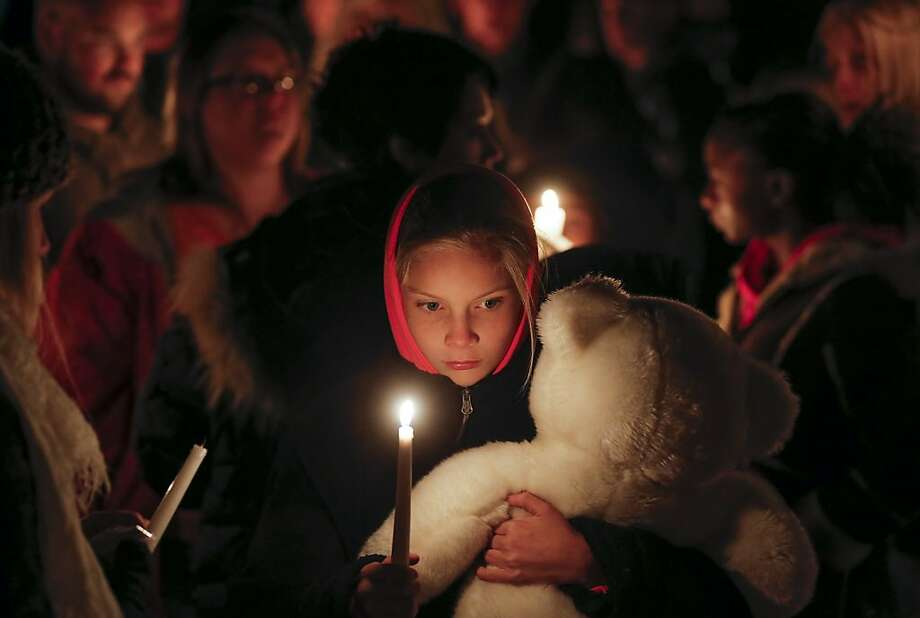 Lexi Umbarger clutches a teddy bear during a candlelight vigil in Parsons, Kan., on Wednesday, Nov. 27, 2013 for Cami Umbarger and her three young children – Hollie, Jaxon and Averie, who were found murdered in their Parsons home on Monday. David Cornell Bennett Jr. of Cherryvale was arrested on Tuesday in connection with the murders. Lexi Umbarger is the niece of Cami Umbarger and was one of nearly 200 people who turned out near the crime scene for the vigil. (AP Photo/The Wichita Eagle, Travis Heying) Photo: Travis Heying, Associated Press