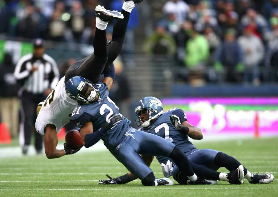 Seahawks players Kelly Jennings (21) and Jordan Babineaux (27) upend New Orleans Saints player Julius Jones during an NFL playoff wildcard game Jan. 8, 2011,  in Seattle. Photo: Joshua Trujillo, Joshua Trujillo/seattlepi.com / Seattlepi.com