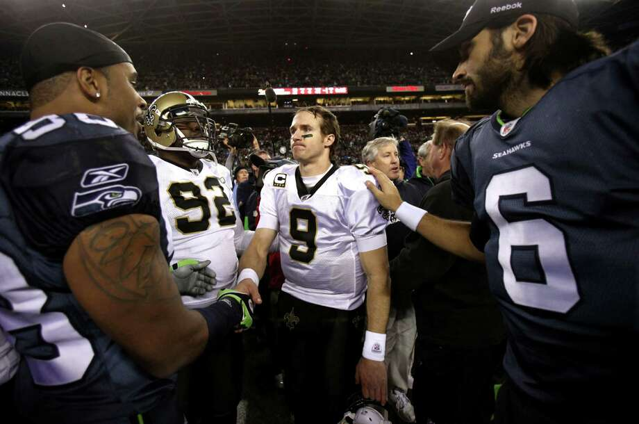 Saints quarterback Drew Brees is greeted by Seahawks players Raheem Brock, left, and Charlie Whitehurst after the Seahawks defeated the Saints in an NFL playoff wildcard game Jan. 8, 2011,  in Seattle. Photo: Joshua Trujillo, Joshua Trujillo/seattlepi.com / Seattlepi.com