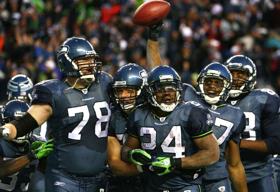 Seattle Seahawks players celebrate a fourth-quarter touchdown by Marshawn Lynch against the defending Super 