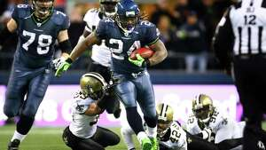 Seattle Seahawks running back Marshawn Lynch breaks through New Orleans defenders during a 67 yard touchdown run in the fourth quarter against the defending Super Bowl champs during an NFL playoff wildcard game in Seattle. The Hawks defeated the Saints 41 to 36. (Joshua Trujillo, Seattlepi.com)