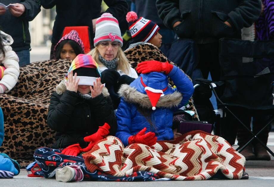 "Left, Kailee Frost, 11, left, Terri Foreman, center and Rylee Frost, 9, right, wait for the parade to start along Walker Street. Foreman, the two cousins' grandma said that she brought the girls' daddies growing up and now she brings them. ""We've been doing this for 30 years."" Photo: Cody Duty, Houston Chronicle"