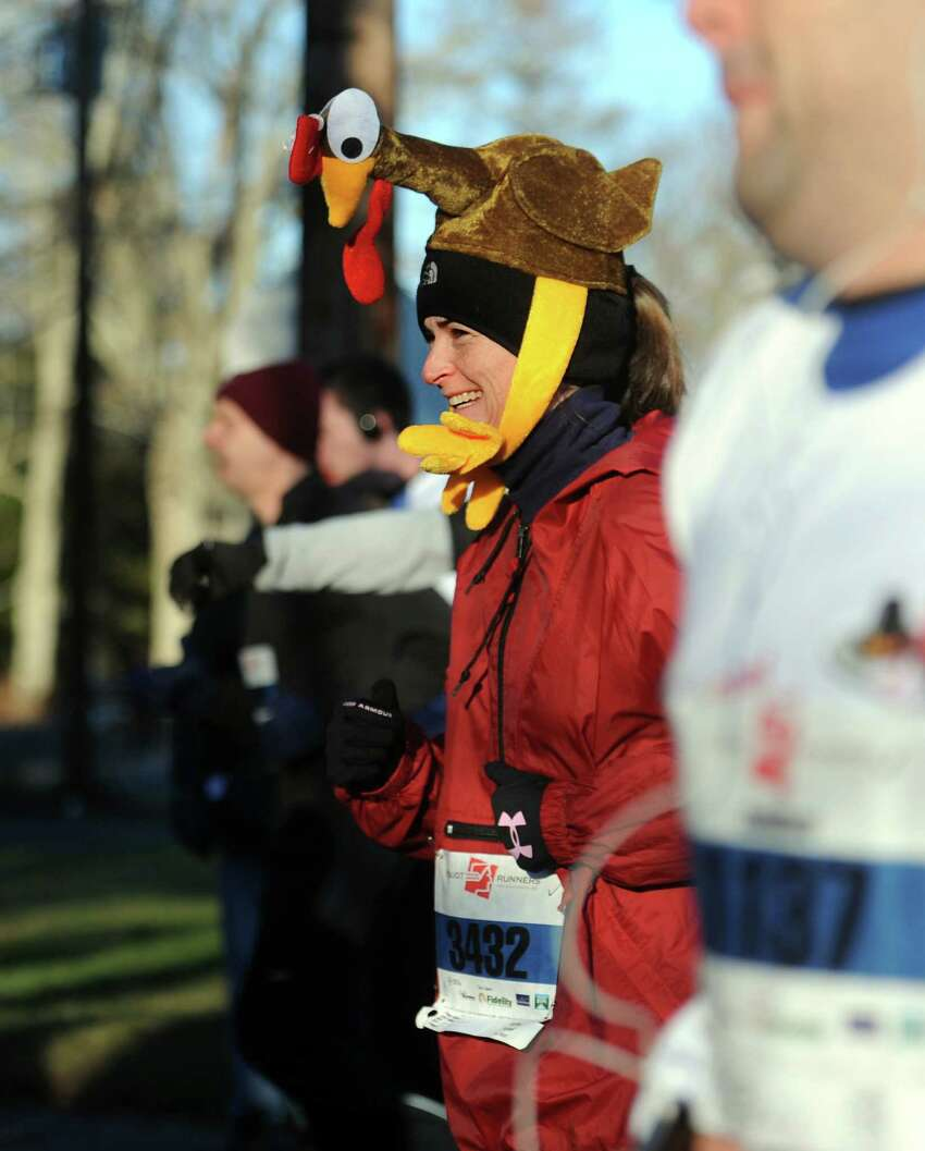 Megan Powell, of Darien, wears her turkey hat as she runs in the annual Pequot Road Runners Thanksgiving Day 5 Mile Road Race Thursday, Nov. 28, 2013 in Southport, Conn.